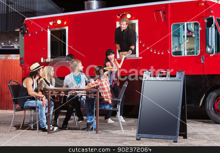 Chef Serves Pizza from Food Truck stock photo, Chef serving food at mobile restaurant with blank sign by Scott Griessel