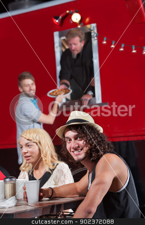 Smiling Man with Friends at Food Truck stock photo, Caucasian male at table with friends ordering pizza by Scott Griessel