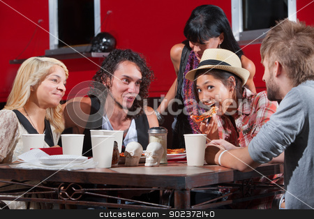 Playing with Pizza stock photo, Friends playing with pizza outside at table by Scott Griessel