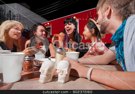 Cheerful Friends Eating Pizza stock photo, Cheerful group of people with pizza slices outside near food truck by Scott Griessel