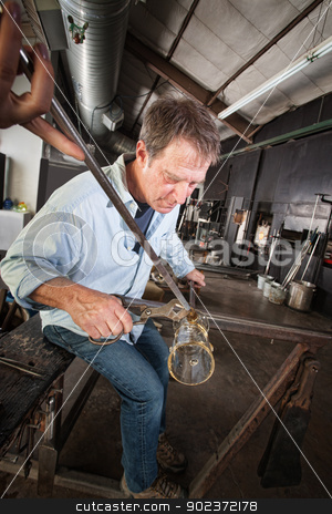Man Finishing Vase stock photo, Mature European man shaping a newly created glass object by Scott Griessel