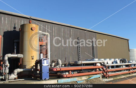Industrial building exterior stock photo, Exterior of modern industrial factory building with tank and pipes. by Martin Crowdy