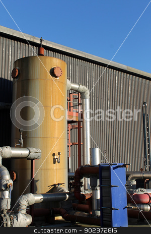 Industrial building stock photo, Tank and pipes outside industrial building. by Martin Crowdy