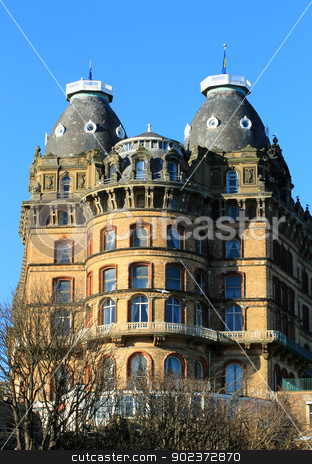 Old gothic hotel building stock photo, Exterior of old gothic style hotel building with blue sky background. by Martin Crowdy