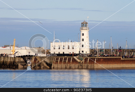 Scarborough harbor lighthouse stock photo, Scarborough, North Yorkshire, England, March 02 2013: Photograph of Scarborough harbor lighthouse seen across the South Bay, North Yorkshire, England. by Martin Crowdy