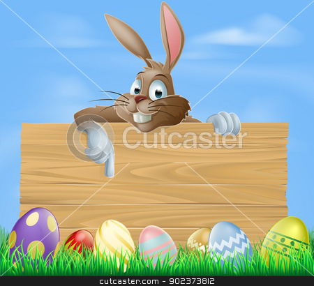 Cartoon Easter bunny pointing stock vector clipart, Cartoon Easter bunny pointing at blank wooden sign with painted chocolate Easter eggs in green field by Christos Georghiou