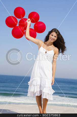 Beautiful girl holding red ballons stock photo, Beautiful girl with red ballons in the beach  by ikostudio