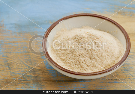 baobab fruit powder stock photo, small ceramic bowl of African baobab fruit powder against grunge painted wood background by Marek Uliasz