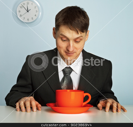 Businessman drinking a very strong and  hot coffee stock photo, Businessman going to drink a very strong and very hot coffee by Alexey Romanov