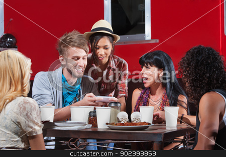 Friends Looking at Text Messages stock photo, Friends eating out and looking over text messages by Scott Griessel