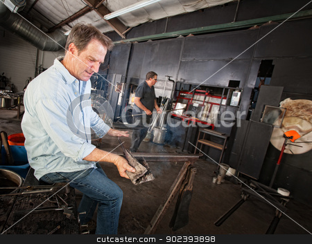 Man Cleans Iron Tool stock photo, Adult male cleaning glass making tools in workshop by Scott Griessel