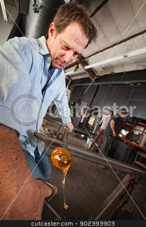 Man Forms Glass Object stock photo, Mature glass artisan forming hot molten object by Scott Griessel