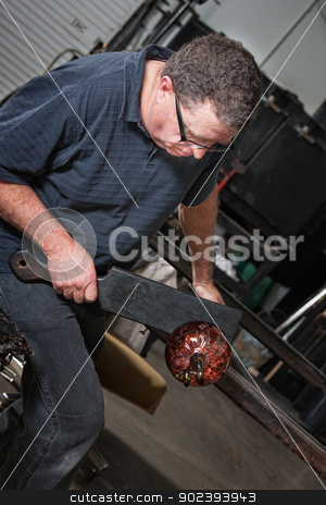 Artist Finishing Glass Bowl stock photo, Glass artist cutting a glass bowl with tool in workshop by Scott Griessel