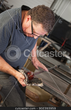 Artist Rolling Hot Glass Piece stock photo, Artist rolling hot glass object with mitts on workbench by Scott Griessel