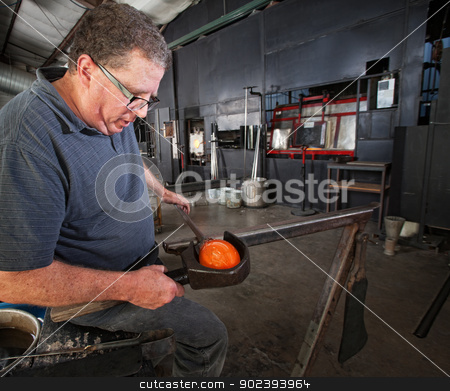 Glass Worker Clamping Glass stock photo, Middle aged glass worker clamping a round vase by Scott Griessel