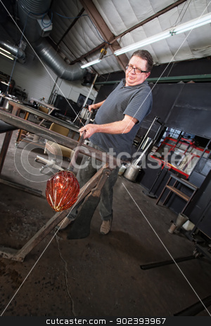 Man Working with Glass Object stock photo, Mature European man handling new glass art object with iron rod by Scott Griessel