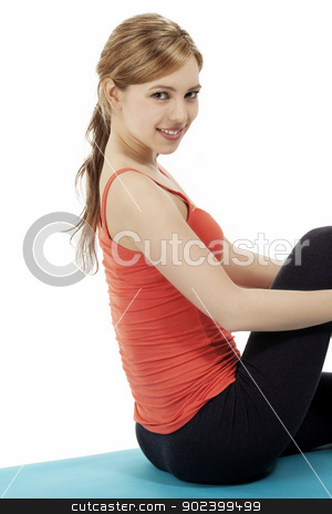 fitness woman sitting on a blue mat making a break on white background