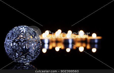 metal christmas ball in front of tea candles on a black mirror