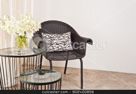 Brown rattan Chair in interior setting stock photo, Brown rattan Chair in interior setting in front of a white wall by Ulrich Schade