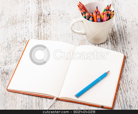 Colorful pencils and notebook stock photo, White cup with colorful pencils and notebook by Grafvision
