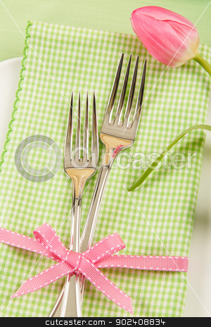 Spring Place Setting With Forks and Tulip stock photo, A fresh Spring place setting shows two forks on a green checkered napkin decorated with a pink bow and tulip. by Karen Sarraga