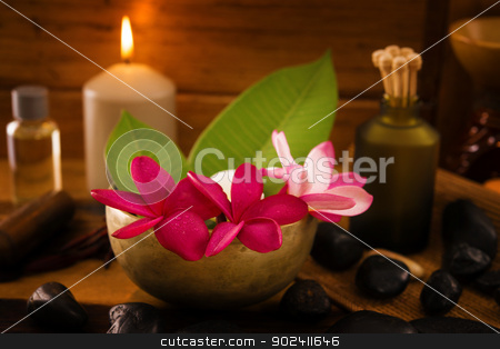 Zen concept. stock photo, Spa setting with frangipani flower, essential oil, zen stones and aromatic candles on table, Zen concept. by szefei