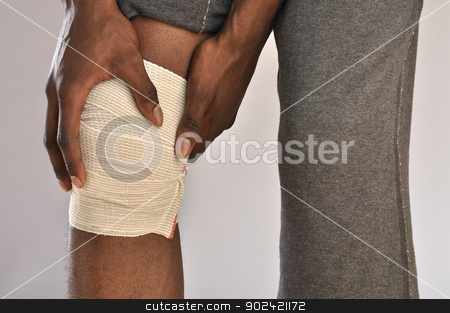 Knee pain stock photo, Closeup of male athlete clutching knee wrapped in sports bandage on grey background by Chad Zuber