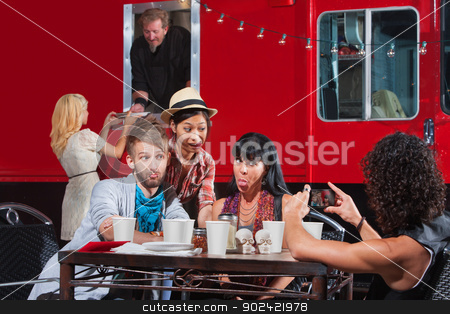 Taking Pictures at Mobile Cafe stock photo, Friends sticking out tongues for photo near food truck by Scott Griessel