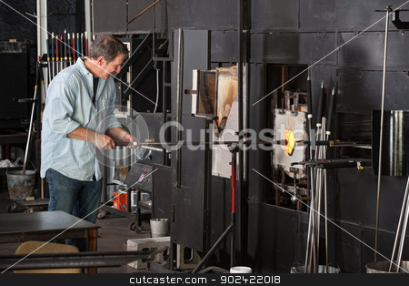 Man Working with Kiln stock photo, European male working with kiln in glass manufacturing business by Scott Griessel