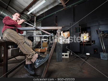 Worker Blowing Glass stock photo, Wide angle view of artisan blowing into fine art glass by Scott Griessel