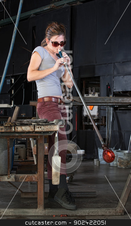 Young Artist Blows Into Glass stock photo, Young industrial artist blowing into new glass art by Scott Griessel