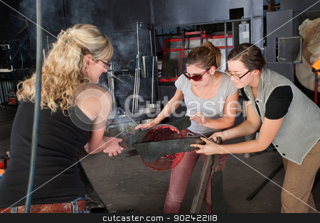 Three Artists Working with Hot Glass stock photo, Three Caucasian women working on glass art creation by Scott Griessel
