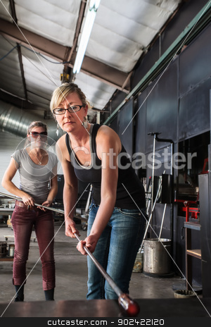 Lady Working with Molten Glass stock photo, Blond glass artist working with molten glass object by Scott Griessel