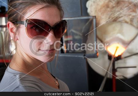 Cheerful Woman Near Kiln stock photo, Cheerful female glass artisan near hot furnace by Scott Griessel