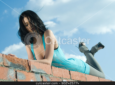 Young woman on roof stock photo, Young woman resting on residential building roof by Aikon