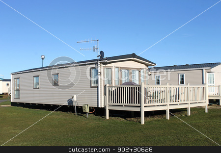 Modern caravan home in trailer park stock photo, Modern caravan home in trailer park with blue sky background. by Martin Crowdy