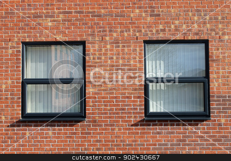 Office windows in brick building stock photo, Two office windows in modern red brick office building. by Martin Crowdy