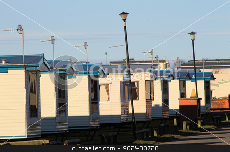 Row of caravans in trailer park stock photo, Row of caravans in trailer park at sunset. by Martin Crowdy