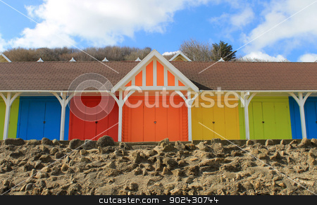Row of colorful beach chalets stock photo, Row of colorful beach chalets with blue sky and cloudscape background. by Martin Crowdy