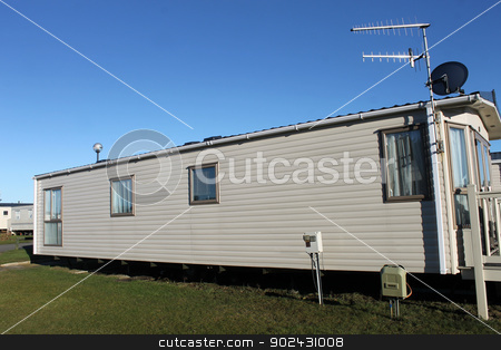 Trailer in caravan park stock photo, Exterior of modern trailer in caravan park, blue sky background. by Martin Crowdy