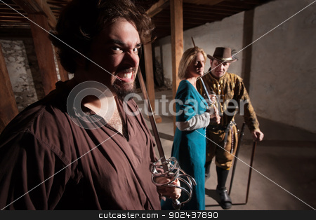 Snarling Swordsman with Friends stock photo, Snarling Caucasian man with tough friends in medieval character by Scott Griessel