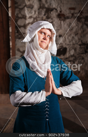 Sinister Nun in Prayer stock photo, Sinister middle ages nun in blue with hands together in prayer by Scott Griessel
