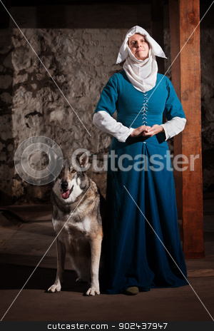 Nun with Dog Indoors stock photo, Peaceful medieval nun standing with pet dog by Scott Griessel