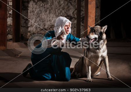 Nun Commanding Dog stock photo, Kneeling middle ages nun character giving commands to a dog by Scott Griessel