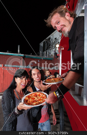 Chef at Order Window with Customers stock photo, Smiling customers with food truck owner and pepperoni pizza by Scott Griessel