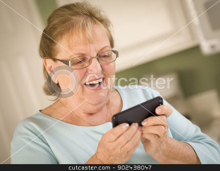 Senior Adult Woman Texting on Smart Cell Phone stock photo, Happy Senior Adult Woman Texting on Her Smart Cell Phone in Kitchen. by Andy Dean