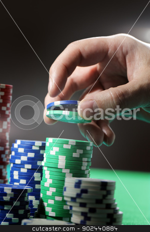Gambling stock photo, Man lifting two gambling chips from stacks with his hand. by Stocksnapper