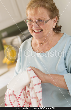 Senior Adult Woman Drying Bowl At Sink in Kitchen stock photo, Smiling Senior Adult Woman Drying Bowl At Sink in Kitchen. by Andy Dean