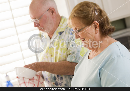 Senior Adult Couple Washing Dishes Together Inside Kitchen stock photo, Senior Adult Couple Having Fun Washing Dishes Together Inside Kitchen of Their House. by Andy Dean