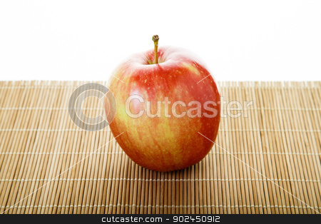 One Macintosh Apple on Mat stock photo, Single red apple on a bamboo mat by Darryl Brooks